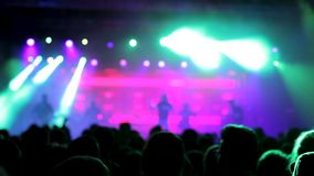 Härliga ljus exponerar folkmassan på en rockbandkapacitet arkivfilmer