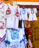 Härliga ljusa etniska skjortor och borddukar med traditionell ungersk broderi i ett gatalager arkivfoto