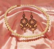 Härliga ljuskronaörhängen och pärlemorfärg halsband Arkivbild