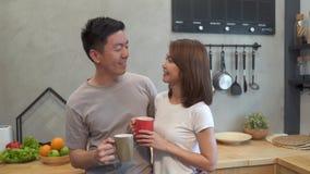 Härliga lyckliga asiatiska par dricker en kopp kaffe tillsammans i köket Man och kvinna som talar, medan ha frukosten stock video