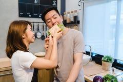Härliga lyckliga asiatiska par matar sig i köket Royaltyfria Foton