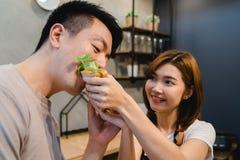 Härliga lyckliga asiatiska par matar sig i köket Arkivbilder