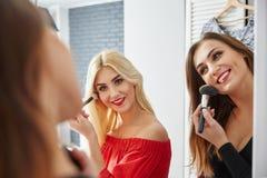 Härliga lyckliga damer som hemma gör makeup Arkivfoton