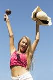 Härliga lyckliga flickahänder upp med den i halvfigur maracas och hatten Royaltyfri Bild