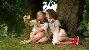 Härliga lyckliga flickasysterstudenter som sitter i, parkerar utomhus på gräs De har vilar ta en selfie förbi arkivfilmer