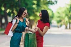 Härliga lyckliga kvinnlig i solexponeringsglas som ser in i shoppingpåsar som går på gatan Positiv sinnesrörelser och shopping royaltyfria bilder