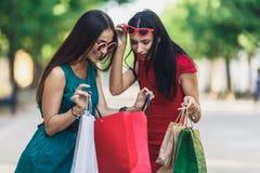 Härliga lyckliga kvinnlig i solexponeringsglas som ser in i shoppingpåsar som går på gatan Positiv sinnesrörelser och shopping royaltyfri fotografi