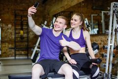 Härliga lyckliga par i sportswearen som gör selfie genom att använda smartphonen royaltyfri bild