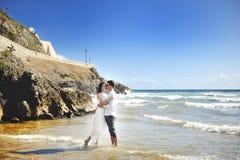 Härliga lyckliga par som omfamnar tillsammans på stranden, Sperlonga, Italien Royaltyfria Bilder
