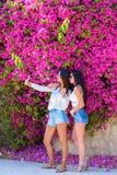 H?rliga lyckliga unga kvinnor g?r selfie p? f?rgrik naturlig bakgrund av ljusa rosa blommor royaltyfria bilder