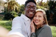 Härliga mellan skilda raser par som gör en selfie royaltyfri bild