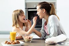 H?rliga moder- och dottermatningss?desslag till varandra hemma arkivfoto