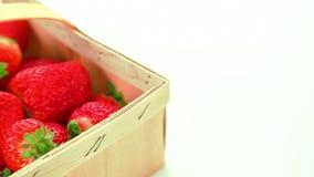 Härliga mogna röda jordgubbar i korg på vit bakgrund arkivfilmer