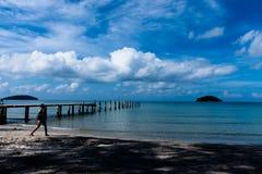Härliga moln och gångare och broar i den blåa himlen utöver det lugna havet arkivbilder