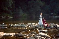 Härliga nygifta personer poserar på kameran under solnedgången Den charmiga röda head bruden står nära sammanträdet fotografering för bildbyråer