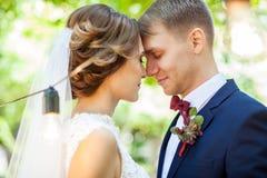 Härliga nygifta personer som sensually in kysser, parkerar royaltyfria foton