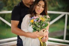 Härliga och lyckliga par som är förälskade med buketten av blommor arkivbilder