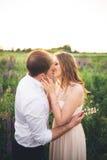 Härliga par, brud, ansar att kyssa och att krama i fältsolnedgången Arkivfoton