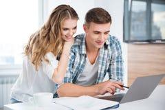 Härliga par genom att använda bärbara datorn och arbete tillsammans Arkivbilder