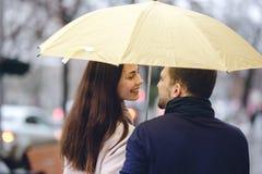 Härliga par, grabben och hans iklädda tillfälliga kläder för flickvän står under paraplyet och ser på de arkivfoton