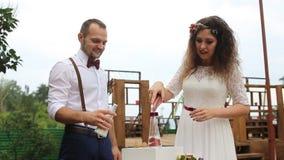 Härliga par hällde i sin tur sand in i flaskan Fyllt med lycka Sandblandningen arkivfilmer