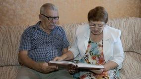 Härliga par i åldern som hemma läser ett boksammanträde på soffan stock video