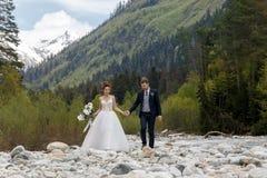Härliga par i bröllopdag på kusten royaltyfria foton
