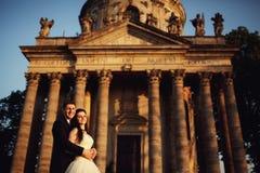 Härliga par i bröllopsklänning utomhus nära antik victoriankyrka Arkivfoton