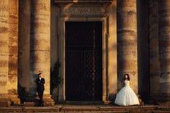 Härliga par i bröllopsklänning utomhus nära den gamla kyrkan Royaltyfria Bilder