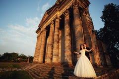 Härliga par i bröllopsklänning utomhus nära den gamla victoriankyrkan Arkivbilder