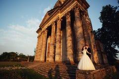 Härliga par i bröllopsklänning utomhus nära gamla kyrkaframdelkolonner Arkivfoton