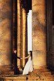 Härliga par i bröllopsklänning utomhus nära kolonner Royaltyfri Bild