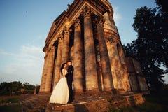 Härliga par i bröllopsklänning utomhus nära victorianstenkyrkan Royaltyfri Bild