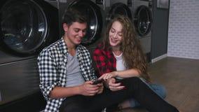 Härliga par i en tvätteri lyssnar till musiken på telefonen, hållande ögonen på video, berättelser Stilig ung man med stock video