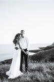 Härliga par i fältet, vänner eller nygifta personen som poserar på solnedgång med perfekt himmel Arkivfoton
