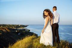 Härliga par i fältet, vänner eller nygifta personen som poserar på solnedgång med perfekt himmel Royaltyfria Foton
