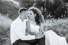 Härliga par i fältet, vänner eller nygifta personen som poserar på solnedgång med perfekt himmel svart white Fotografering för Bildbyråer