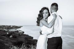 Härliga par i fältet, vänner eller nygifta personen som poserar på solnedgång med perfekt himmel svart white Arkivfoto