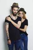 Härliga par i hatt och posera över vit bakgrund tillsammans Hipsterpojke och flicka Arkivfoto