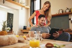 Härliga par, i kök och att använda en touchpad Fotografering för Bildbyråer