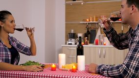 Härliga par i köket som äter på stearinljusljus stock video