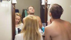 Härliga par, man och kvinna, tvättar sig tillsammans i badrummet framme av spegeln 4k ultrarapid, en man rakar arkivfilmer