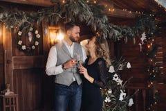 Härliga par med champagne under julkransen royaltyfria foton
