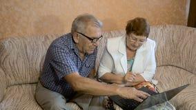 Härliga par på åldern av att arbeta på bärbara datorn hemma stock video