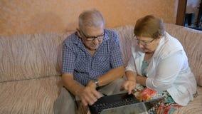 Härliga par på åldern av att arbeta på bärbara datorn hemma arkivfilmer