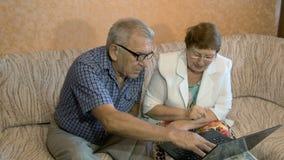 Härliga par på åldern av att arbeta på bärbara datorn hemma lager videofilmer