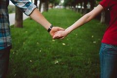 Härliga par rymmer händer i gör grön trädgården Arkivfoton