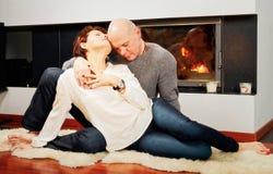 Härliga par sammanträde med passion på pälsmatta nära firepen royaltyfri foto