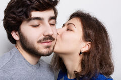 Härliga par som är förälskade över vit bakgrund En flickvän som passionately kysser hans stilfulla pojkvän i haka En bearde Arkivbild