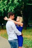 Härliga par som är förälskade med en kvinna som går i en parkera på en bänk som kysser på solnedgången och älskar sig, en blå klä Royaltyfri Fotografi